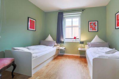 Schlafzimmer mit Einzelbetten im Ferienhaus für 4