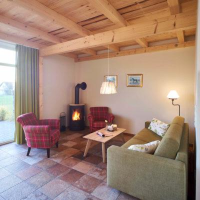 Advent auf Fehmarn Ferienwohnung Sundschlag mit Kamin zwei Sessel grünes Sofa